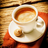 Cup of coffee on a saucer with a mini biscuit royalty free stock images