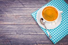 Cup of coffee on saucer with spoon and blue napkin Stock Photos