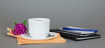 Cup of coffee with saucer, spoon and flower Stock Photos