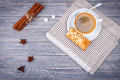 Cup of coffee on saucer with spoon. Vanilla sticks. Star anise and gray napkin Stock Photos