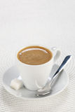 Cup of coffee in a saucer with a spoon  on white wicker a mat Stock Images