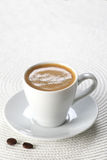 Cup of coffee in a saucer  on white wicker a mat Stock Photos