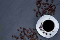 Cup of coffee and scattered coffee beans on wooden surface Stock Photography