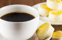 Cup of coffee and scone on wood background, warm toning, selec Royalty Free Stock Images