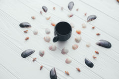 Cup of coffee and sea shells on a white background. Cup of coffee and sea shells on a white wooden background Stock Photos