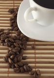 Cup of coffee and seed. A cup of coffee and brown seed near royalty free stock images