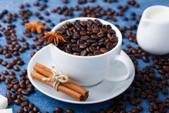 Cup of coffee seeds cinnamon anis close-up macro. Cup of coffee with seeds, cinnamon, anis, milk in a white milk jug, sugar on blue background. Vertical Stock Image