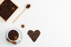 Cup of coffee seeds cinnamon anis hearts wooden box spoon. Cup of coffee seeds, cinnamon, anis coffee heart shapes, wooden box and spoon with coffee Royalty Free Stock Images