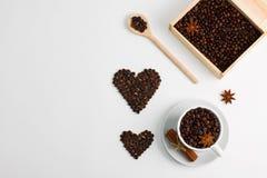 Cup of coffee seeds cinnamon anis hearts wooden box spoon. Cup of coffee seeds, cinnamon, anis coffee heart shapes, wooden box and spoon with coffee Stock Photography