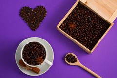 Cup of coffee seeds cinnamon anis hearts wooden box spoon. Cup of coffee seeds, cinnamon, anis coffee heart shapes, wooden box and spoon with coffee Stock Images