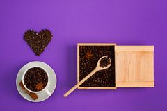 Cup of coffee seeds cinnamon anis hearts wooden box spoon. Cup of coffee seeds, cinnamon, anis coffee heart shapes, wooden box and spoon with coffee Royalty Free Stock Photo