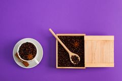Cup of coffee seeds cinnamon anis wooden box spoon. Cup of coffee seeds, cinnamon, anis, wooden box and spoon with coffee on purple background. I love coffee Stock Image