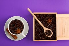 Cup of coffee seeds cinnamon anis wooden box spoon. Cup of coffee seeds, cinnamon, anis, wooden box and spoon with coffee on purple background. I love coffee Royalty Free Stock Images