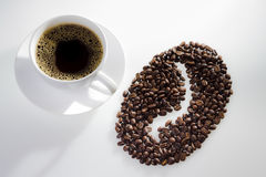 A cup of coffee with seeds and coffee symbol stock image