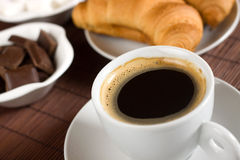 Cup of coffee served with croissants and chocolate Stock Photos