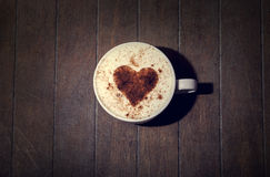 Cup with coffee and shape of the cacao heart on it. Royalty Free Stock Photography