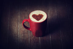 Cup with coffee and shape of the cacao heart on it. Royalty Free Stock Photos