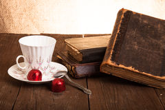 Cup of coffee, shokolad and stack of old books on the old wooden Stock Photos