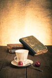 Cup of coffee, shokolad and stack of old books on the old wooden Royalty Free Stock Photos