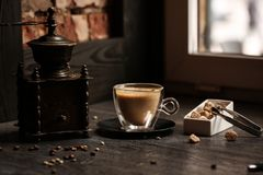 Cup of coffee in coffee shop vintage color. Coffee grinder and Brown cane sugar on wooden table with flare blurred Stock Photo