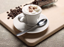 Cup of coffee with a skin and coffee grains Royalty Free Stock Photography