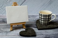 Cup of coffee, small easel with a blank canvas over white, two dark wooden hearts. Old wooden background and big copy royalty free stock photo