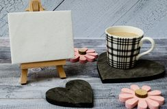 Cup of coffee, small easel with a blank canvas over white, two dark wooden hearts and pink flowers. Old wooden royalty free stock images