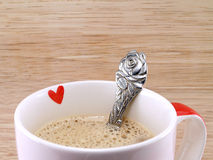 closeup small red heart on cup of coffee and rose flower shaped silver spoon Stock Photos