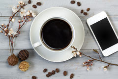 Cup of coffee and smart phone, on wooden table with cherry flowers, chocolate candy and coffee beans, top view Royalty Free Stock Photo