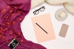 A cup of coffee, smart, pink paper with new years goals. Scarf and Christmas lights on white background. Stock Photo