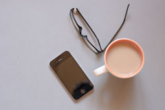 Cup of coffee, smartphone and black glasses. Isolated on white. Sepia. Royalty Free Stock Photography