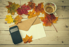 Cup of coffee with smartphone and letter decorated with autumn l Royalty Free Stock Photos