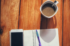 Cup of coffee, Smartphone and pen put on notebook Stock Photos