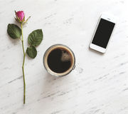Cup of coffee, smartphone and a pink rose on marble background Royalty Free Stock Images