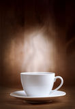 Cup of coffee with smoke. On brown background Royalty Free Stock Photos