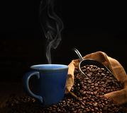 Cup of coffee with smoke and coffee beans Royalty Free Stock Images