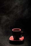A cup of coffee with smoke on black background. Toned Stock Image