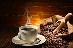 Cup of coffee with smoke and coffee beans Stock Photos