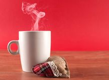 Cup of coffee with smoke and heart on wooden desk on red stock photo