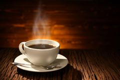 Cup of coffee with smoke on old wooden Royalty Free Stock Photo