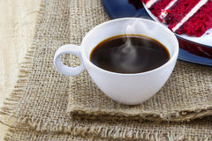 Cup of coffee with smoke on a sack and wooden table Royalty Free Stock Images
