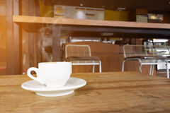 Cup of coffee with smoke on wooden table in cafe. Royalty Free Stock Photos
