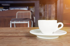 Cup of coffee with smoke on wooden table in cafe. Royalty Free Stock Images