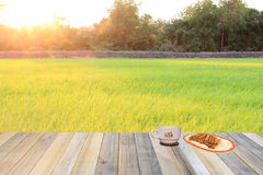 Cup of coffee and snacks  on wooden and rice fields background Royalty Free Stock Photography