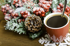 Cup coffee, snowflake and Christmas wreath with pine cones. Royalty Free Stock Images