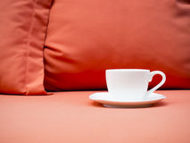 Cup of coffee on sofa with pillow Royalty Free Stock Image