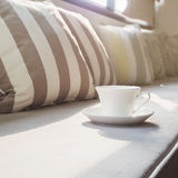 Cup of Coffee on sofa with pillows Stock Photos