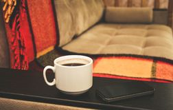 A cup of coffee is on the sofa table, next is a mobile phone, home comfort stock photography