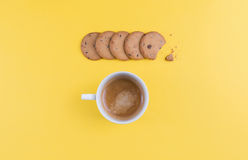 Cup of coffee some biscuits on a yellow table royalty free stock photos
