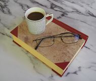 A cup of coffee and some books. A cup of coffee, glasses and some books on marble background royalty free stock photo